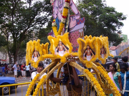 Pierced penitent bearing cross-shaped kavadi and the glory of the god, followed by family women